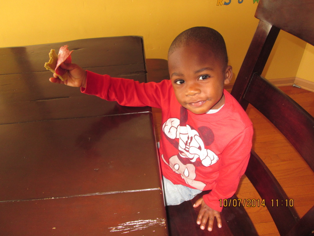 Isaiah enjoying his plantain bread with some meat.
